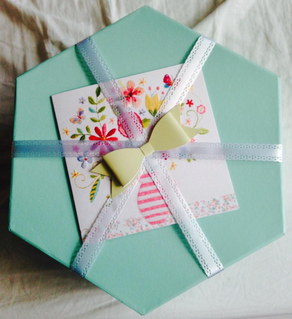 Bild på paketet. Det är en ljusturkos låda med vita spetsband runt, en gul rosett och ett kort med blomster i vas på.