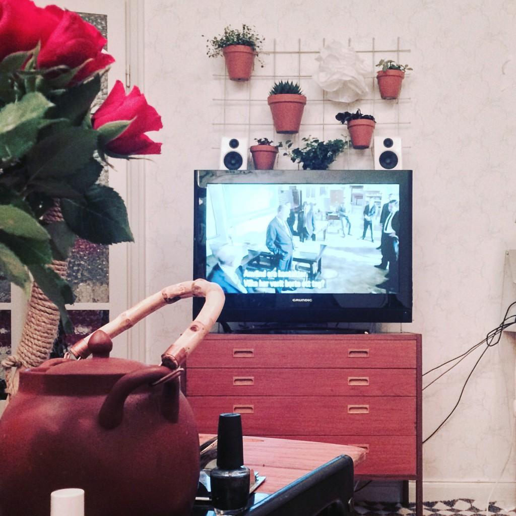 Bild på nätet bakom teven. Byrån de står på syns och i förgrunden är det rosor, tekanna och nagellack.